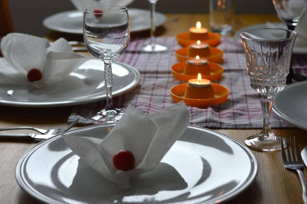 Ein Ermangelung diverser Haushaltsgegenstände: Eierbecher statt Kerzenmständer. Küchenpapier statt Servietten. Tomaten statt Blumen.